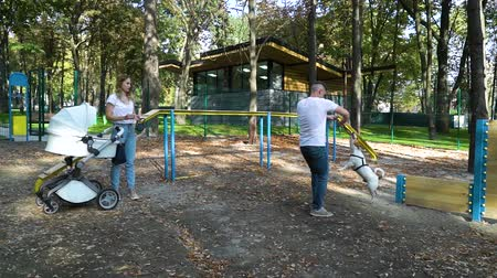 jovial : Cheerful family with baby and dog on playground Vídeos