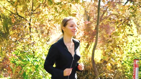 energický : Sporty fit girl jogging in autumn park