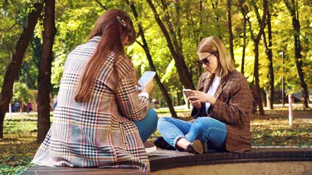 obsession : Hipster girls surfing social media on smartphones outdoors Stock Footage