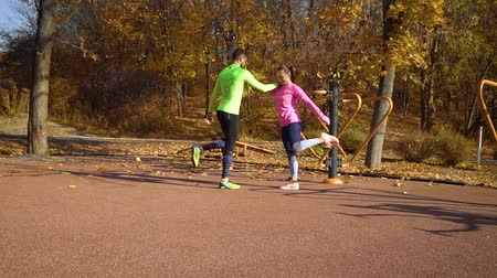 autumn leaves : Athletic couple stretching legs on sports ground in pair on sunny day