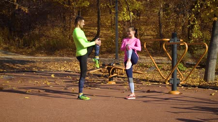 legginsy : Athletic couple warming up and stretching legs on sports ground on autumn day Wideo