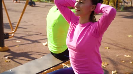 hasi : Fit couple working out abdominal exercises on sports ground in the morning Stock mozgókép