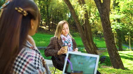 jovial : Fellow students sitting in park and preparing homework