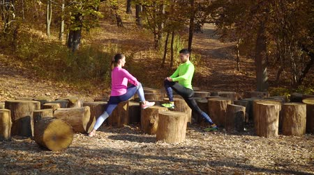 tree stump : Couple of athletes stretching legs on wood logs in autumn forest Stock Footage