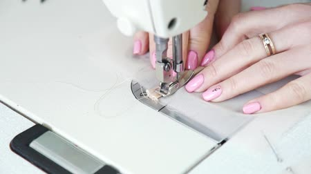closeup of young seamstress hands sewing tulle fabric with sewing machine