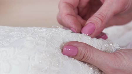 closeup of neat hands of young woman stitching beads to elegant lace fabric