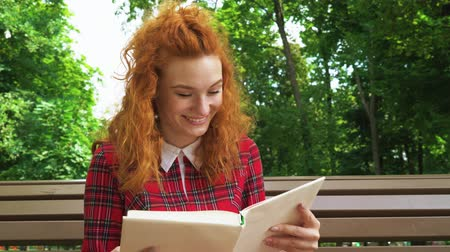 Jovial red haired girl laughing at funny book in park