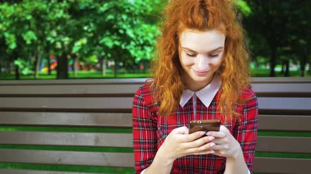 Smiling girl with red hair texting on smartphone in park