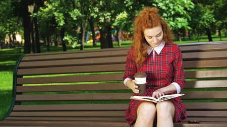 Red haired student studying in park and drinking coffee Стоковые видеозаписи