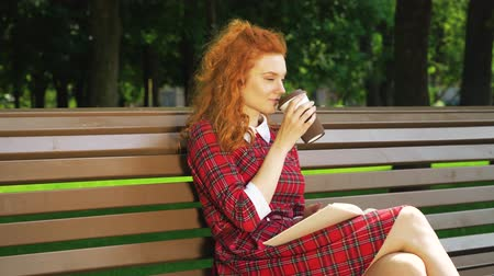 Beautiful red haired girl relaxing in park with book and coffee Стоковые видеозаписи