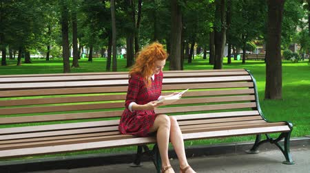 Redhead girl reading funny book in park