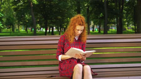 Pretty girl reading sad book in green park