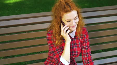 Happy beautiful girl talking on smartphone in green park