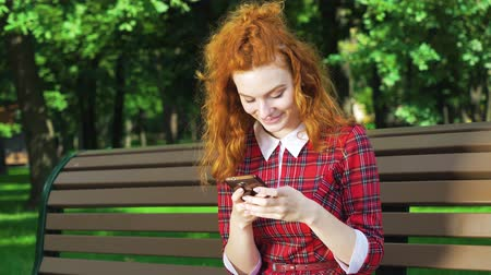 Adorable redhead girl typing message on smartphone in green park