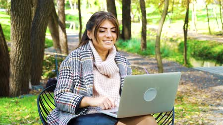 Successful speaker using laptop for presenting webinar sitting in park Stock Footage