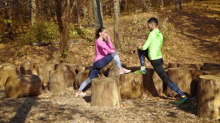 Athletic couple training together outside in autumn forest Stock Footage