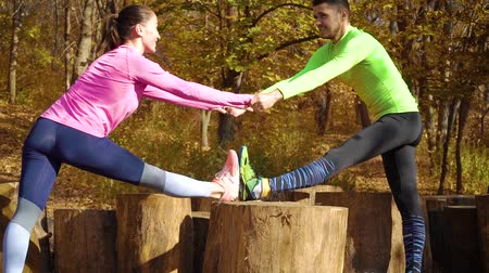 Happy couple holding hands and exercising in autumn forest Стоковые видеозаписи