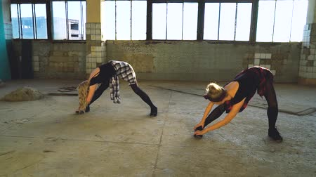 Pretty blonde dancers stretching in old factory building