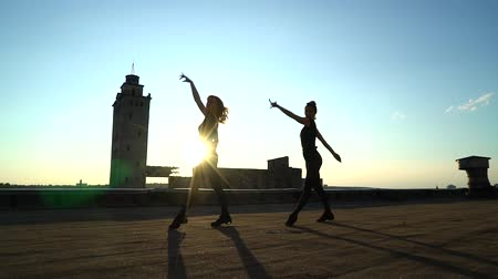 Silhouette of girls dancing in pair on roof at sunset