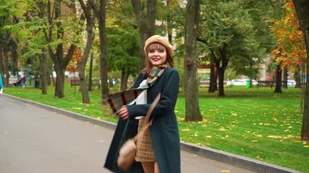 Smiling girl in elegant outfit walking in autumn park Стоковые видеозаписи