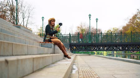 Fashion vlogger using smartphone and steadicam for recording video in park Videos
