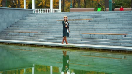 Moody girl walking in park and reflecting in lake water