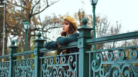 Depressed girl standing on bridge in park