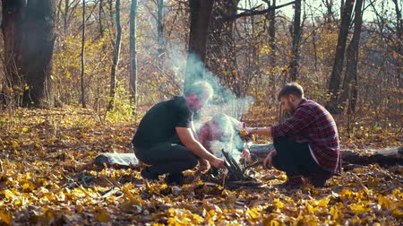 Friends making campfire in autumn forest