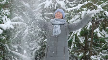 happy woman throws snow in the air in pine forest on winter day in slow motion