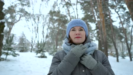 portrait of smiling woman walking in winter park