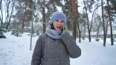 adult woman talking on the phone in winter park Стоковые видеозаписи