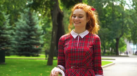 andar : Adorable red haired girl walking with umbrella in sunny park