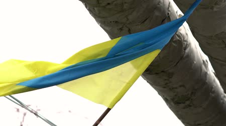 szakadt : Ukrainian flag swaying under heating pipes outside
