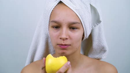 mole : Happy teenage girl in bath towel eating apple Stock Footage