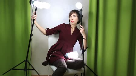 eleganckie : Beautiful emotional model posing at camera with light equipment.