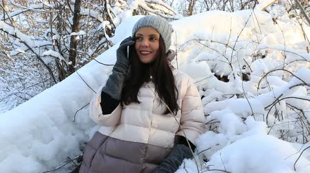 шляпа : Beautiful happy girl talking on the smartphone. Snow covered trees in winter park.