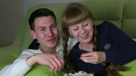 radość : Young couple with popcorn watching comedy on television and laugh.