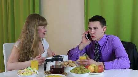núpcias : Young woman trying to communicate with her husband at breakfast. He pays no attention to it. Business man talking on smartphone. Stock Footage