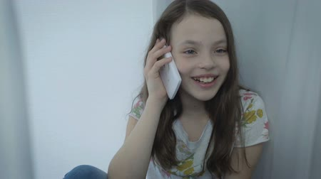 telefon : Beautiful happy little girl emotional talking on the smartphone by window.