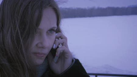 zmrazit : Frozen girl calling on smartphones. Guy is late for date.