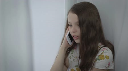 telefon : Beautiful little girl emotional talking on smart phone by window. Stock mozgókép