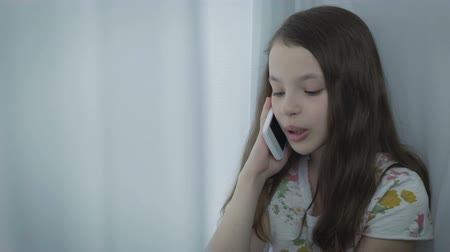 telefon : Beautiful little girl emotional talking on smart phone Stock mozgókép