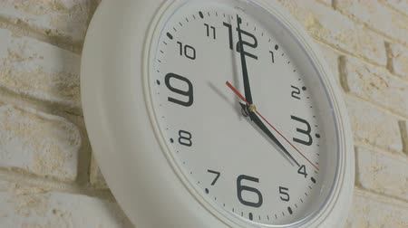 minute hand : Time four hour. Timelapse. Round white clock hanging on brick wall.