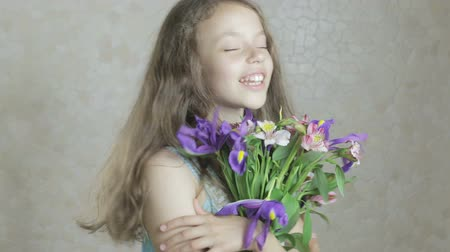 alstroemeria : Beautiful happy girl enjoys a bouquet flowers of irises and alstroemeria.