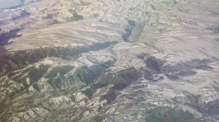 moğolistan : Mongolia aerial view of mountains covered with snow in spring stock footage video