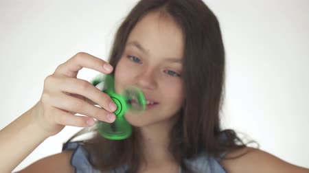 littlegirl : Beautiful cheerful teen girl playing with green fidget spinner on a white background stock footage video