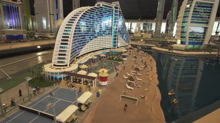 lego : Dubai, UAE - April 01, 2018: Exhibition of mock-ups Jumeirah Beach Hotel and Burj Al Arab Hotel made of Lego pieces in Miniland Legoland at Dubai Parks and Resorts stock footage video Stock Footage