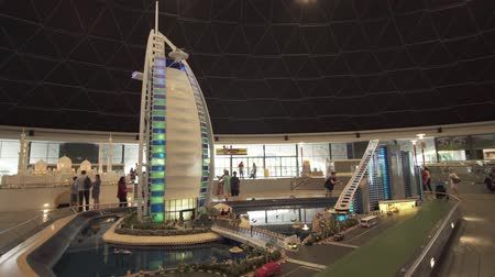 queue : Dubai, UAE - April 01, 2018: Exhibition of mock-ups Jumeirah Beach Hotel and Burj Al Arab Hotel made of Lego pieces in Miniland Legoland at Dubai Parks and Resorts stock footage video Stock Footage