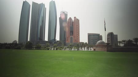 palmtree : Abu Dhabi, UAE - April 04, 2018: Skyscrapers in Abu Dhabi view from the lawn of the hotel Emirates Palace stock footage video
