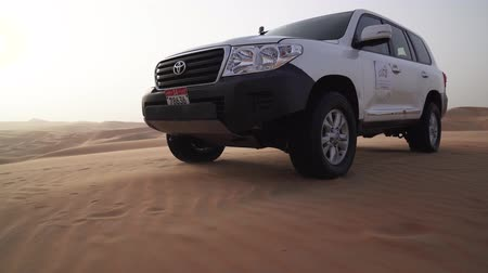 utiliteit : Abu Dhabi, Verenigde Arabische Emiraten - 5 april 2018: SUV op de top van het duin in de Rub al Khali woestijn, de wind achtervolgt de video van de zand stock footage Stockvideo